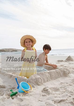 Children building sandcastle on beach