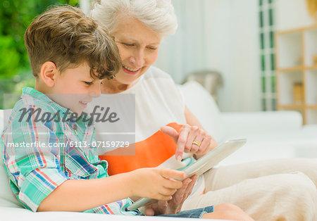 Older woman and grandson using digital tablet