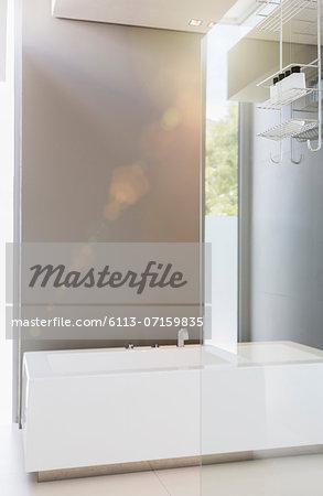Bathtub and glass wall in modern bathroom