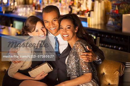 Portrait of well dressed friends hugging in luxury bar