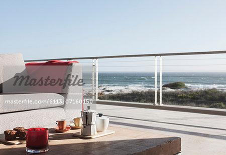 Breakfast on coffee table on modern patio overlooking ocean