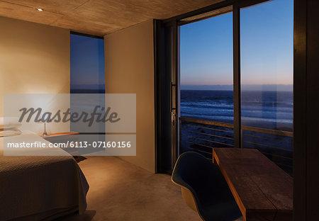 Modern bedroom overlooking ocean at dusk