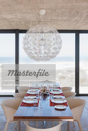 Set table in modern dining room overlooking ocean