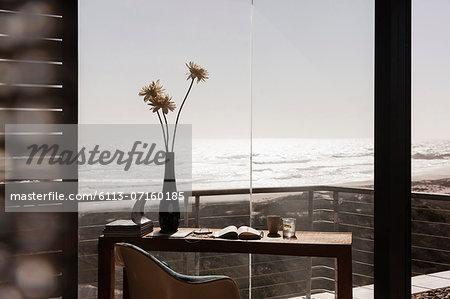 Vase of flowers on desk in modern home office overlooking ocean