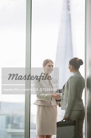 Businesswomen shaking hands in office