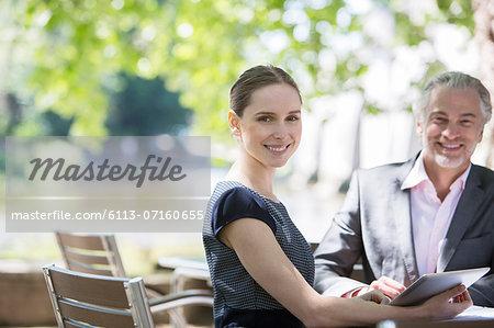 Business people smiling at sidewalk cafe