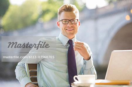 Businessman smiling at sidewalk cafe
