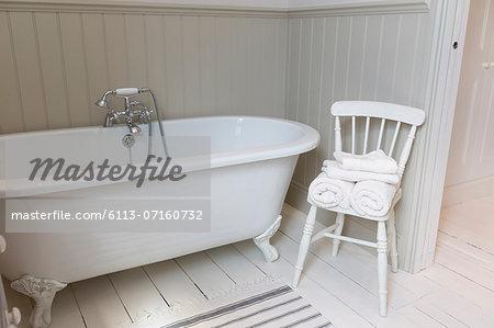 Bathtub and chair in ornate bathroom