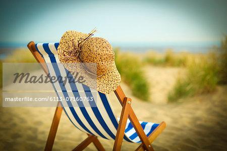 Sun hat on chair on beach