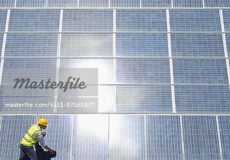 Worker examining solar panels