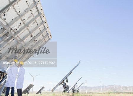 Scientists examining solar panel in rural landscape