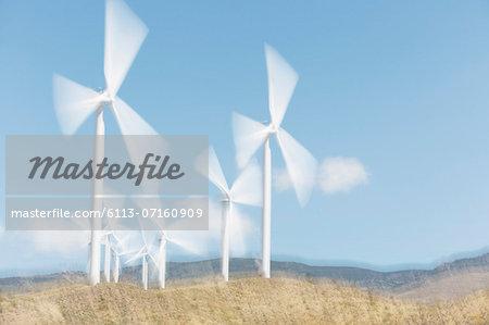 Wind turbines spinning in rural landscape