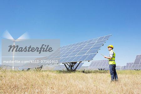 Worker examining solar panels in rural landscape