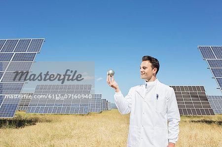 Scientist examining sphere by solar panels