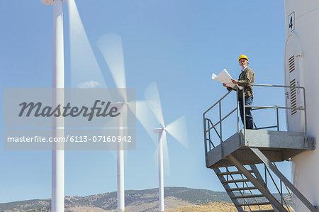 Worker standing on wind turbine in rural landscape