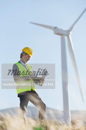 Worker using laptop by wind turbine in rural landscape