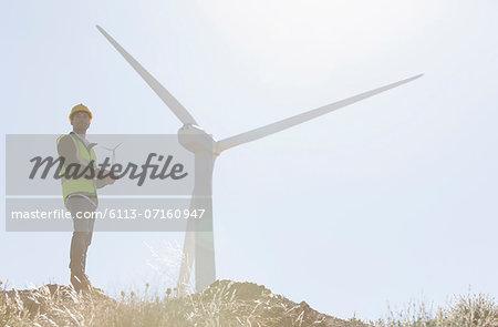 Worker standing by wind turbine in rural landscape