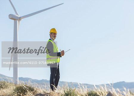 Businessman examining wind turbines in rural landscape