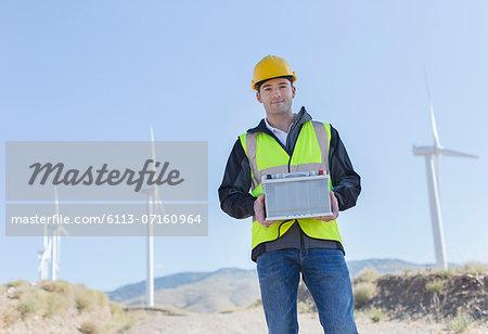 Worker standing by wind turbines in rural landscape