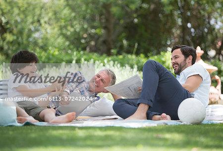 Multi-generation men relaxing on blanket in backyard