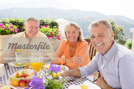 Senior friends enjoying breakfast on balcony