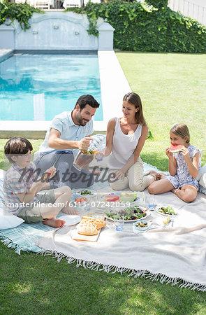 Family enjoying picnic in backyard