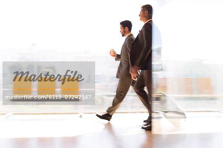 Businessmen walking in airport corridor