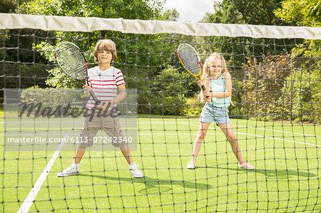 Children playing tennis on grass court