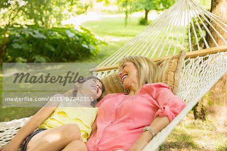 Grandmother and granddaughter relaxing in hammock