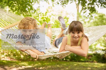 Children relaxing together in hammock