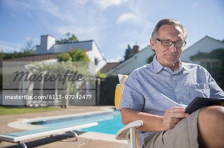 Man using digital tablet at poolside