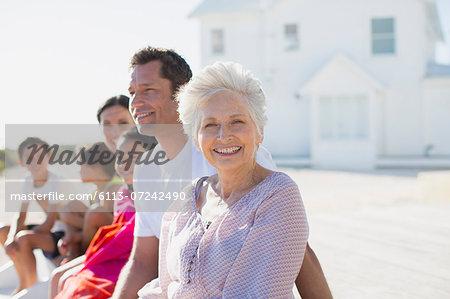 Multi-generation family smiling outside beach house