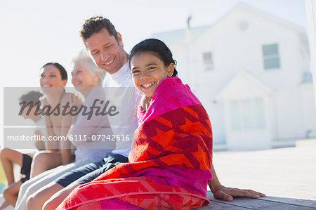 Multi-generation family sitting outside beach house