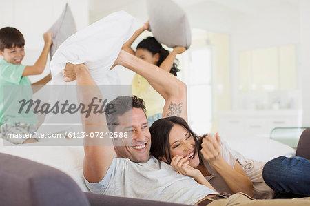 Family enjoying pillow fight in living room