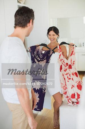 Man helping girlfriend choose dress in bedroom