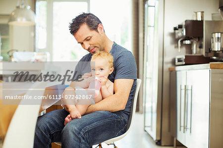 Father feeding baby in kitchen