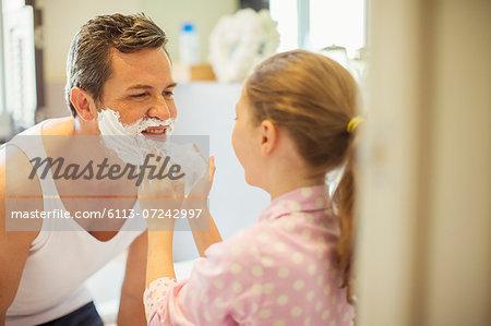 Girl rubbing shaving cream on father's face