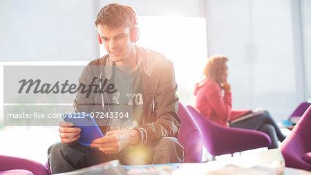 University student listening to headphones in lounge