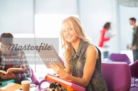 University student using digital tablet in lounge