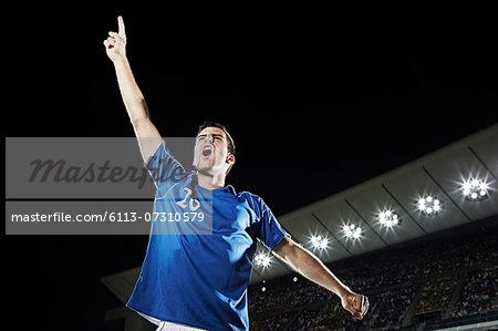 Soccer player cheering in stadium