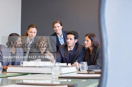 Business people examining model in meeting