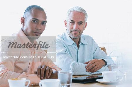 Businessmen using digital tablet in cafe