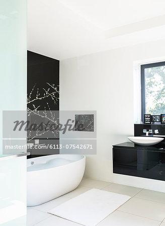 Wall art and soaking tub in modern bathroom