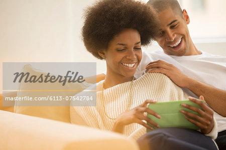 Couple using digital tablet on sofa