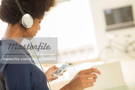 Woman listening to headphones in living room