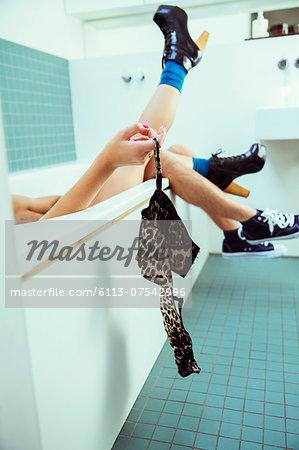 Couple removing woman's bra in bathtub