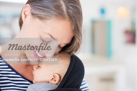 Mother holding sleeping baby boy