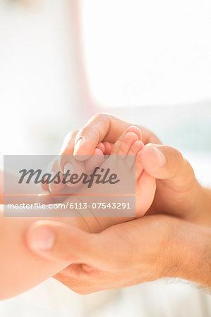 Father cradling baby boy's feet