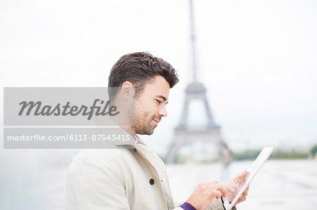 Businessman using digital tablet by Eiffel Tower, Paris, France