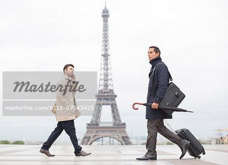 Businessmen walking past Eiffel Tower, Paris, France